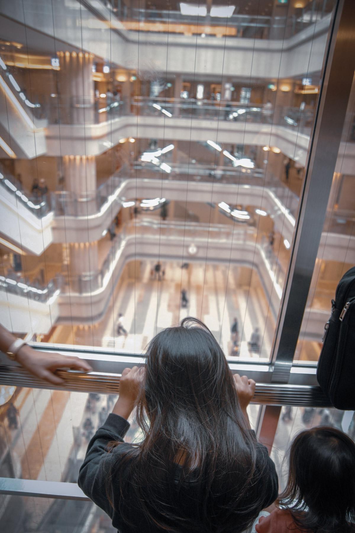 羽田空港第1ターミナル ガラス張りのエレベータと女の子