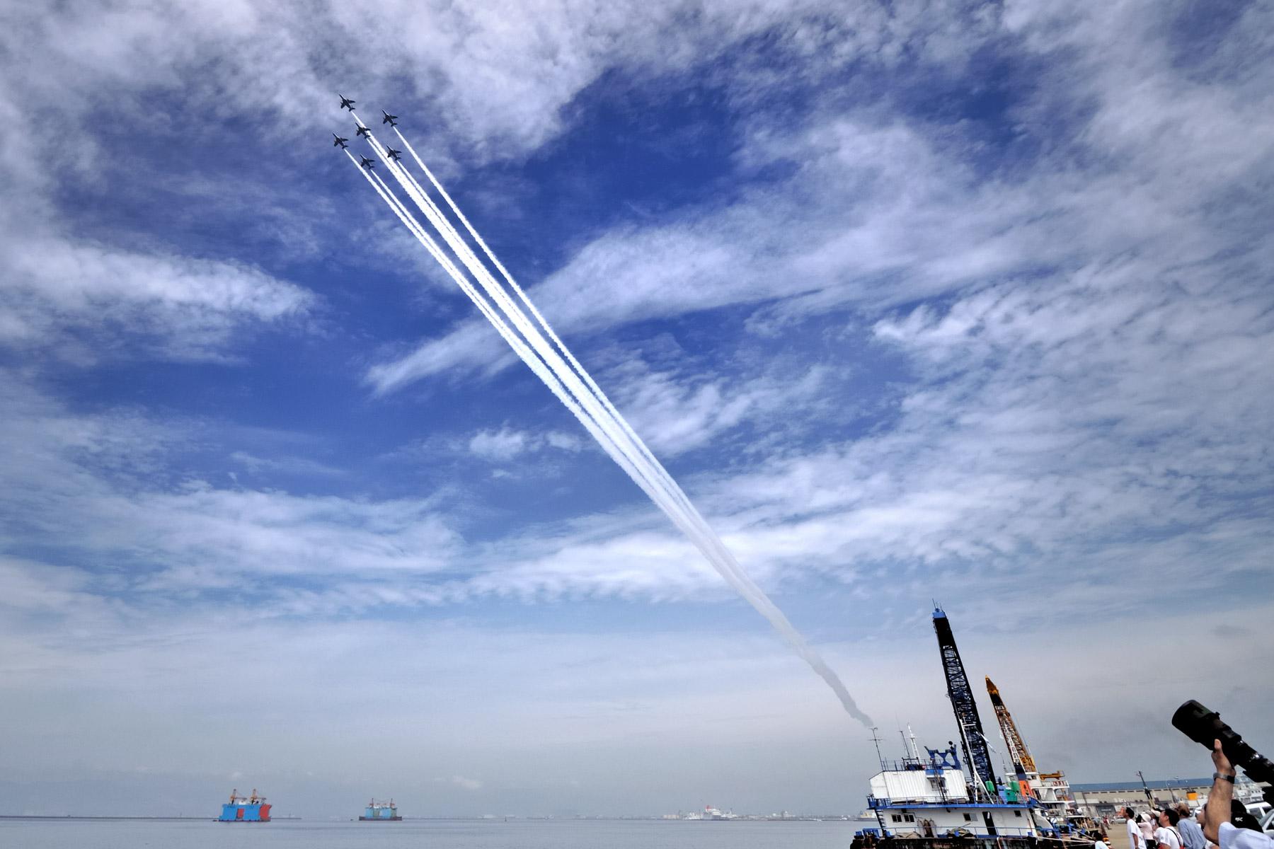 函館湾上空でリハーサル中のブルーインパルス6機編隊 雲の多い青空を貫く6本の白いラインが鮮やか