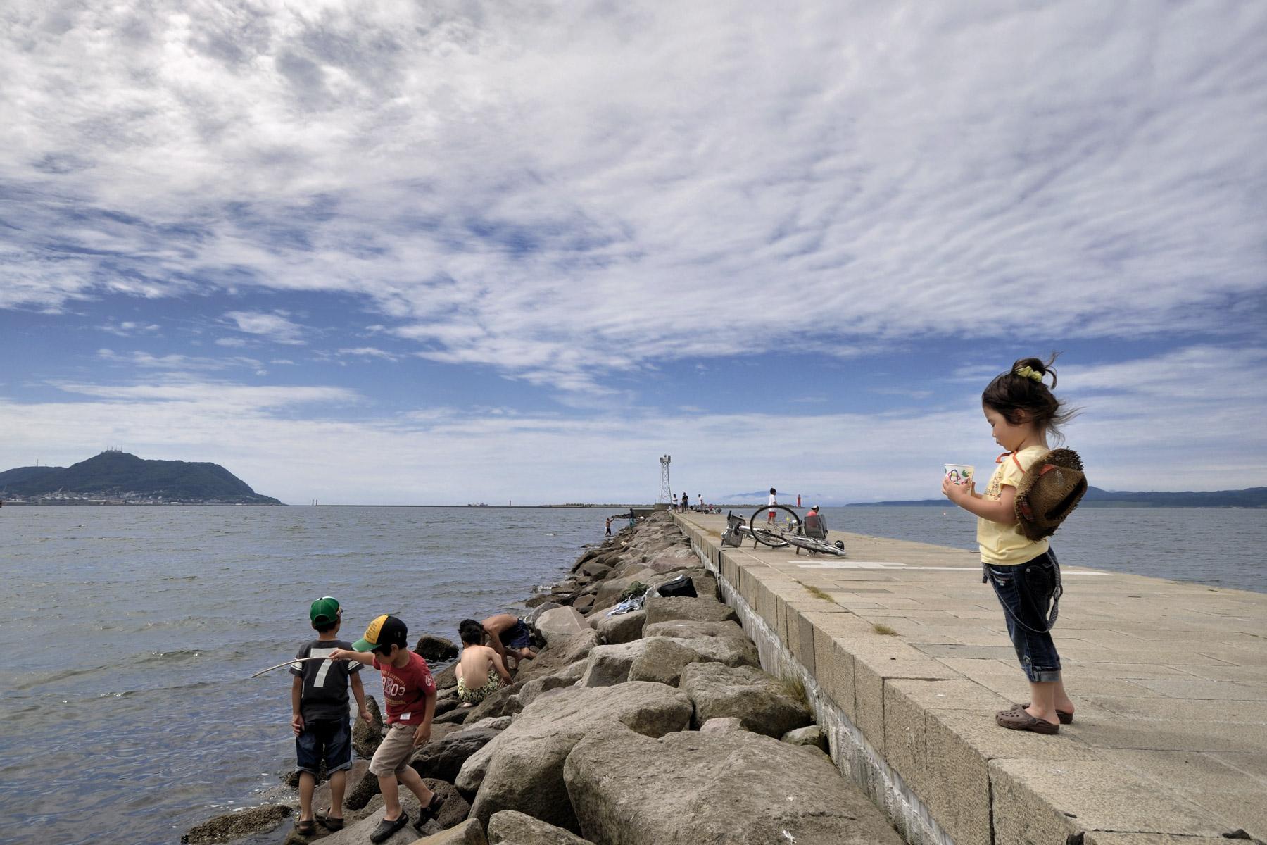 どんよりと暑い夏の日、七重浜海水浴場脇の突堤で遊ぶ子ども達