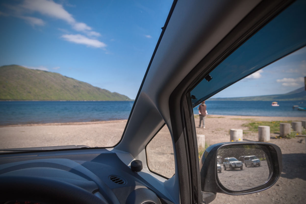 車のフロントガラス越しに見る快晴の支笏湖と砂浜 撮影:NIKON D90 + TOKINA 16-50mm