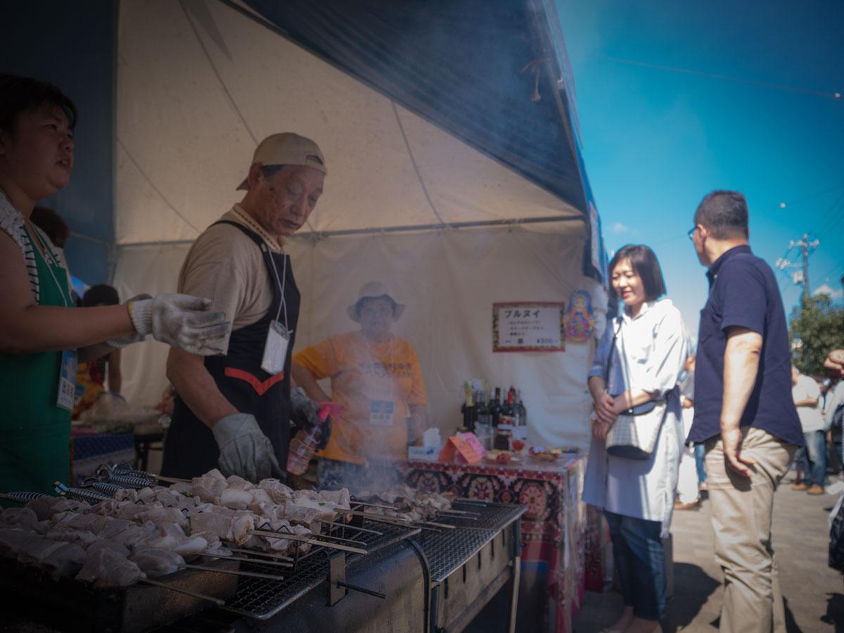 ユジノサハリンスク市(日本ユーラシア協会函館地方支部)ブースで男性がチャシリクを焼いている様子