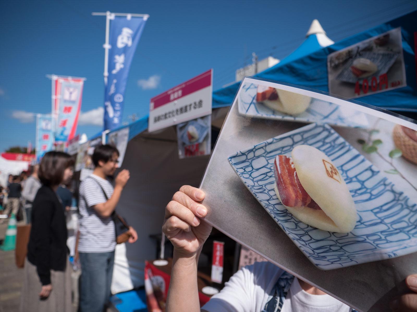 豚の角煮まんの写真を掲げて呼び込みをする女性