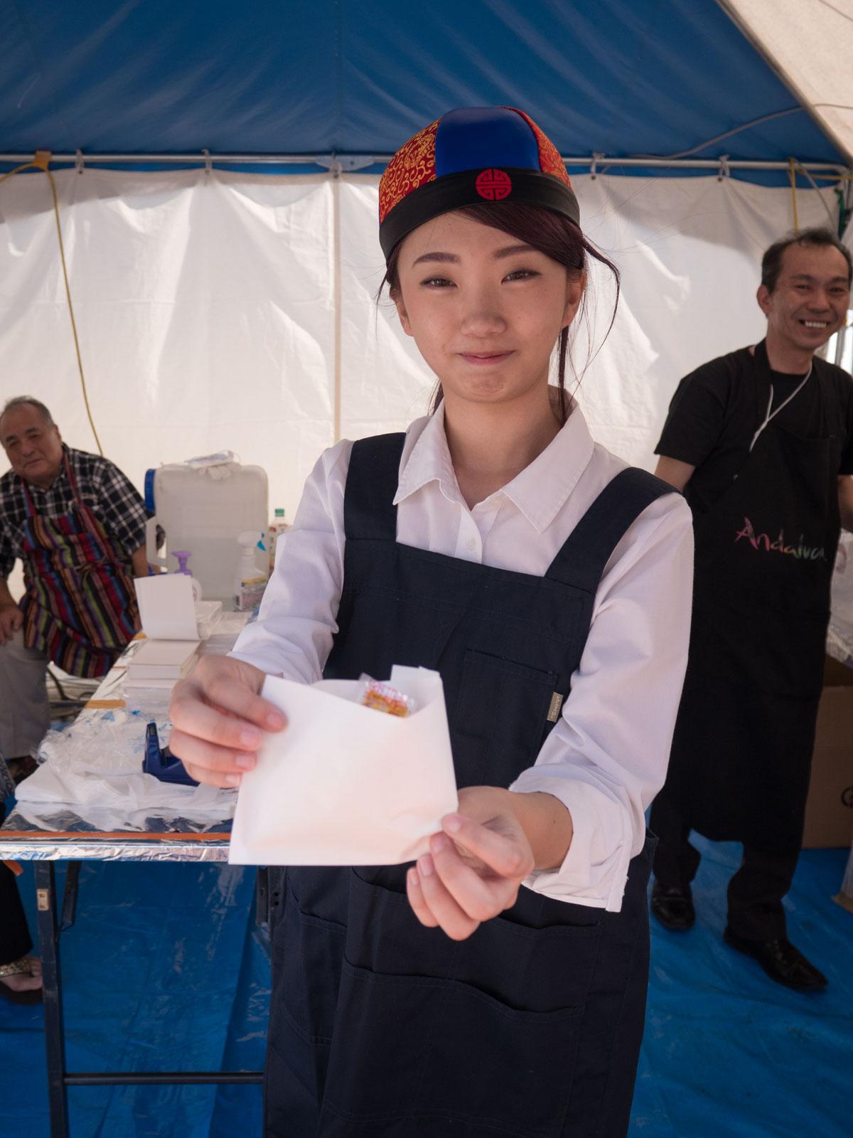 角煮まんを手に、オススメのポーズを取ってくれる美人で小顔の店員の女性