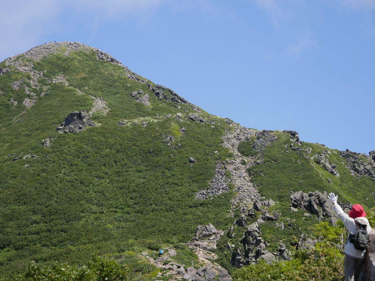 山頂に向かい手を振る女性
