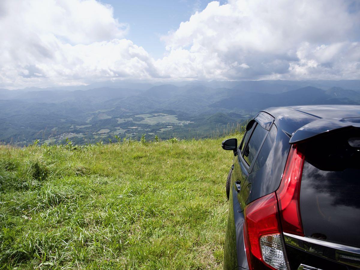 車とともに山麓を見下ろす