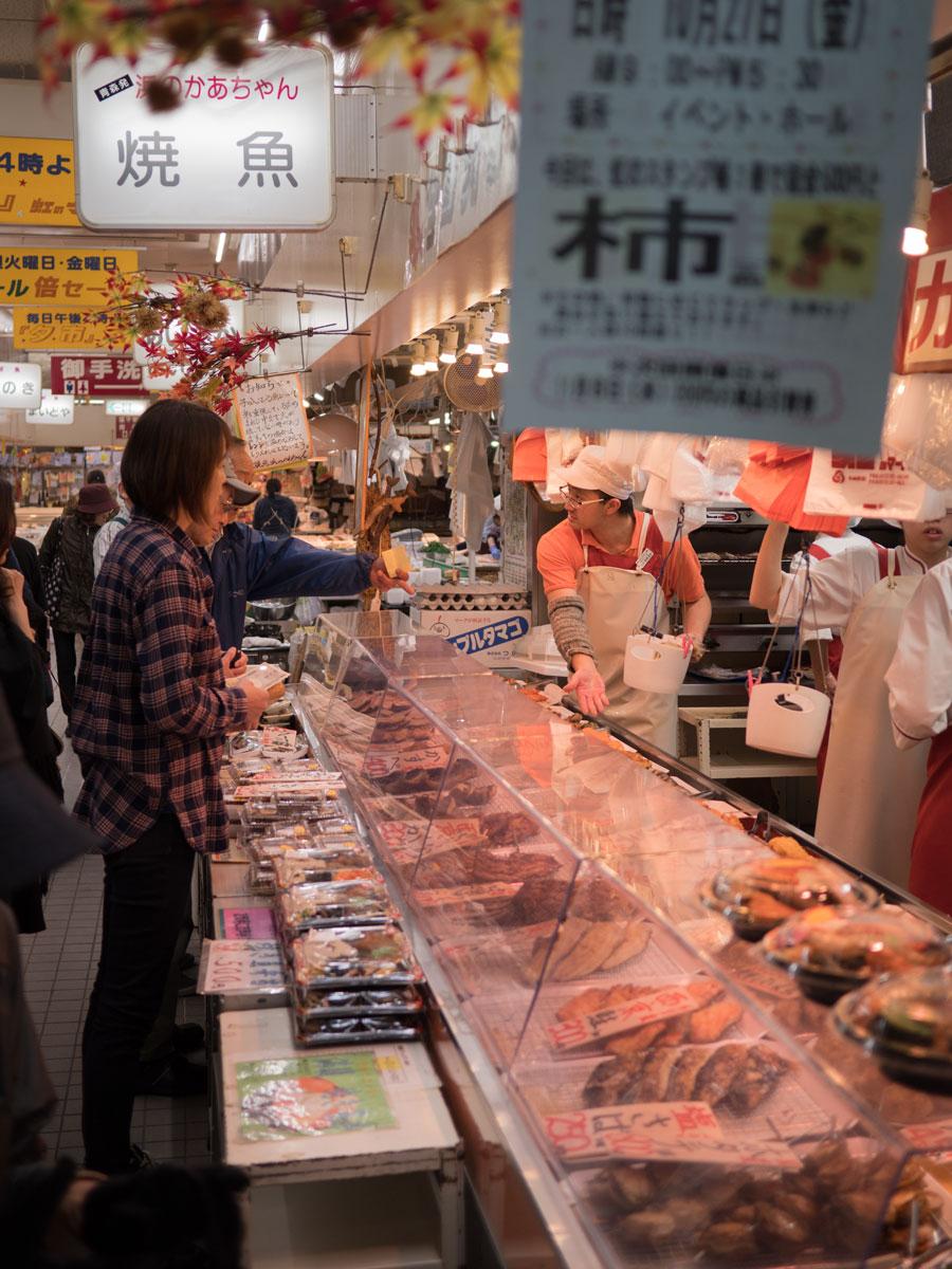 弘前「虹のマート」のオンリー焼き魚の惣菜屋と買い物客 撮影:DMC-GX8 + LEICA DG 12-60mm