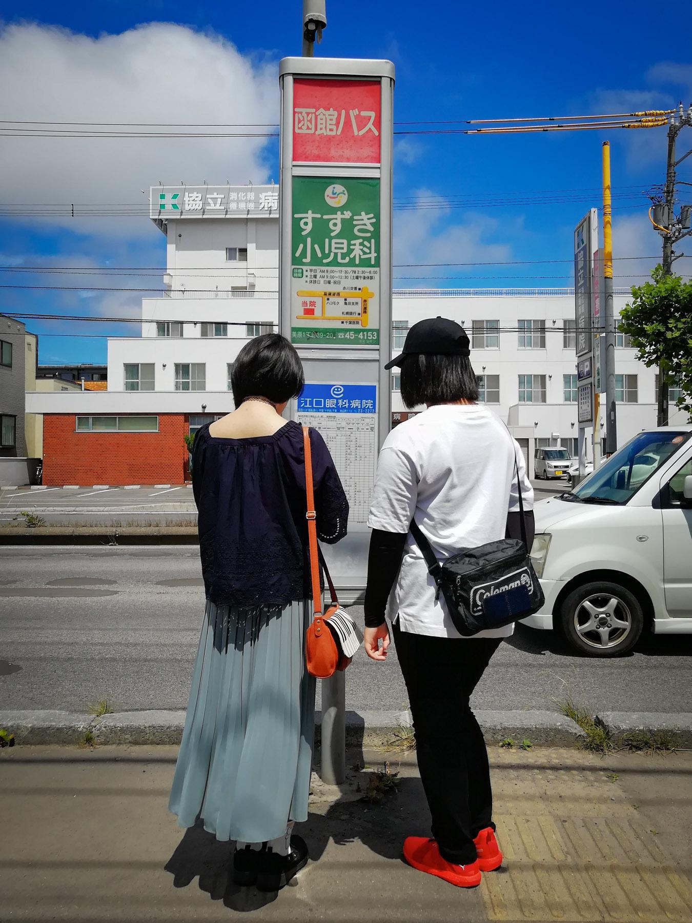 亀田支所前停留所でバスを待つ人