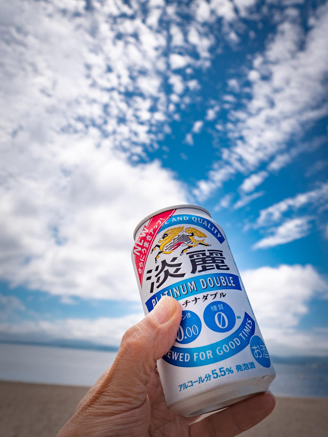 夏空を海を背景に掲げたよく冷えた缶ビール(正確には違うが)