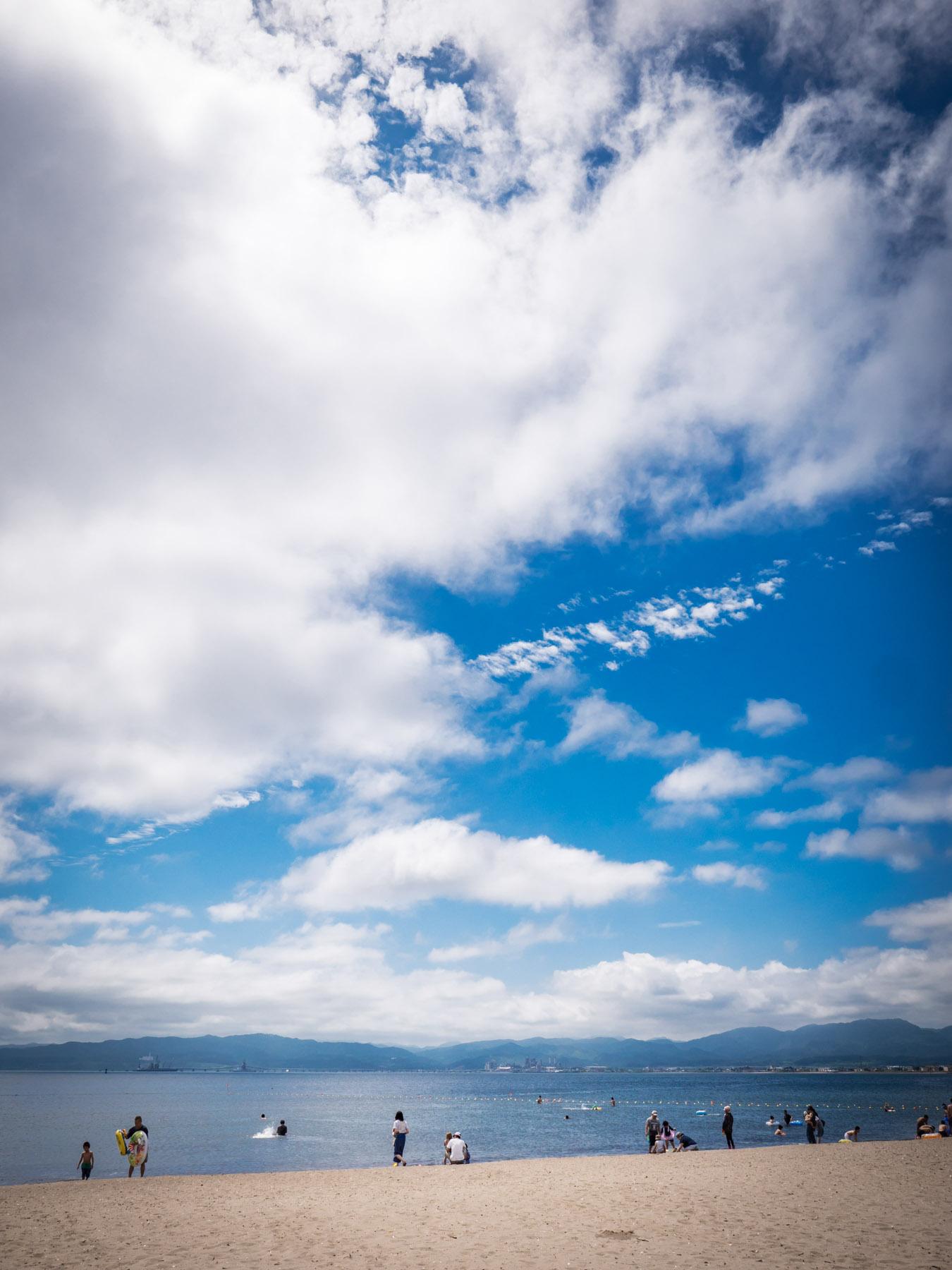 青空と白い雲と砂浜と海水浴客