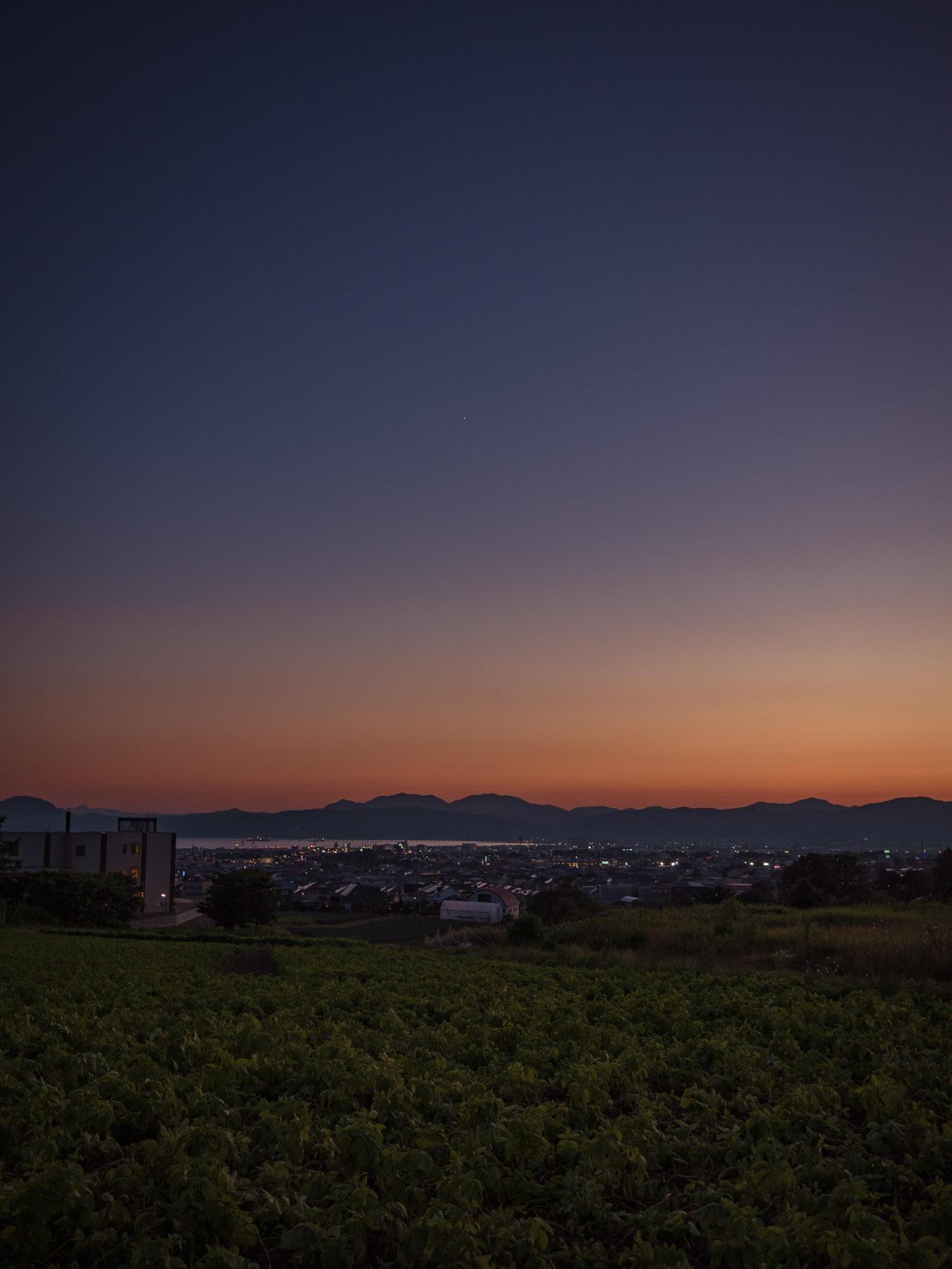 夜の闇に溶けゆく函館湾と市街地と山並みとオレンジ色の地平線
