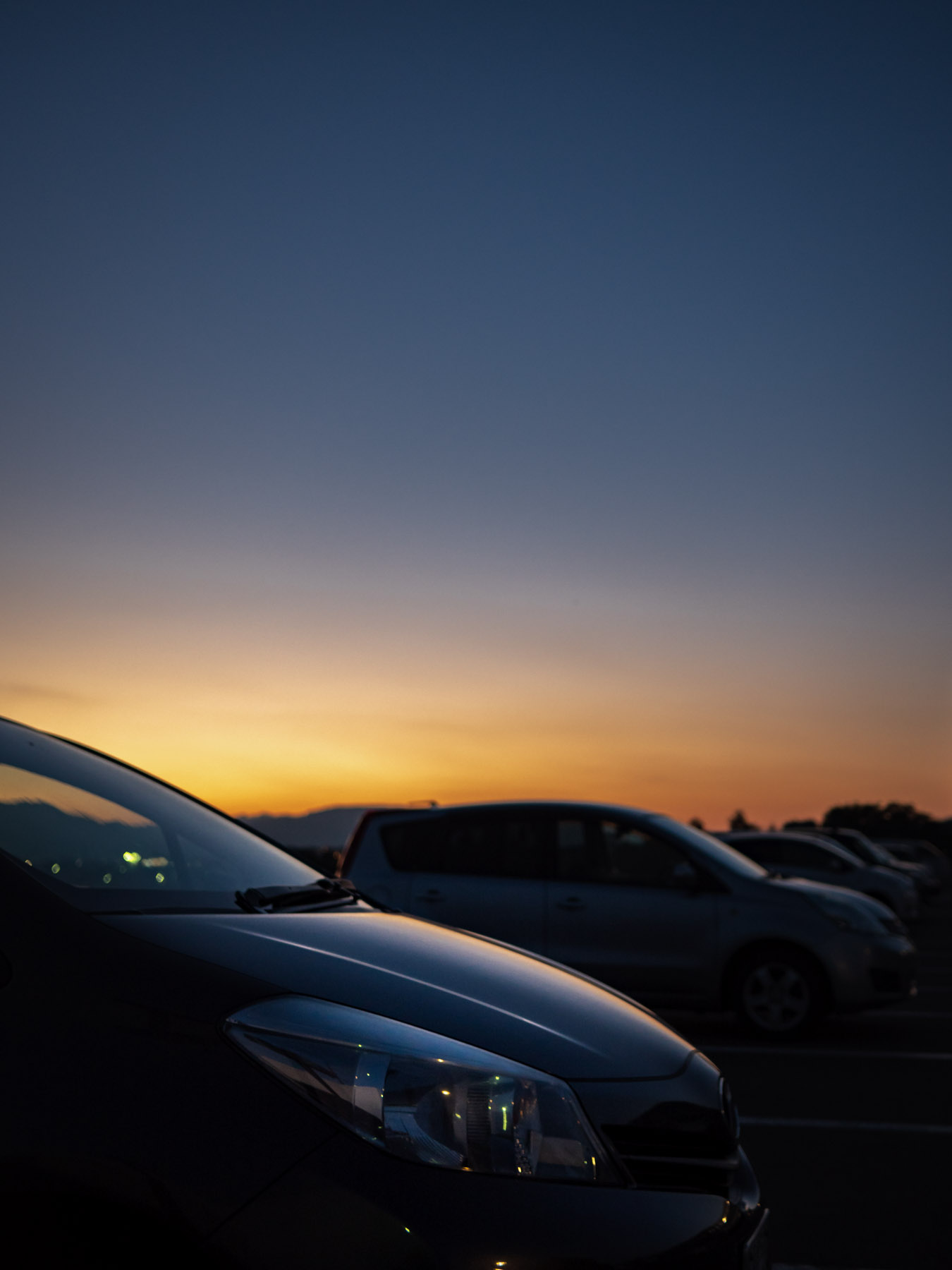 夕闇に消えてゆく車のシルエットとオレンジ色のスカイライン
