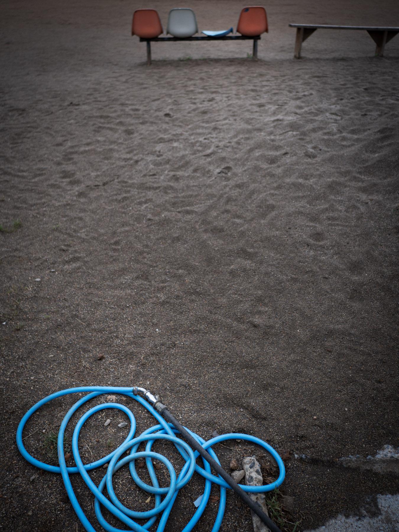 垢が中学校グランドの散水ホースと壊れかけたベンチ