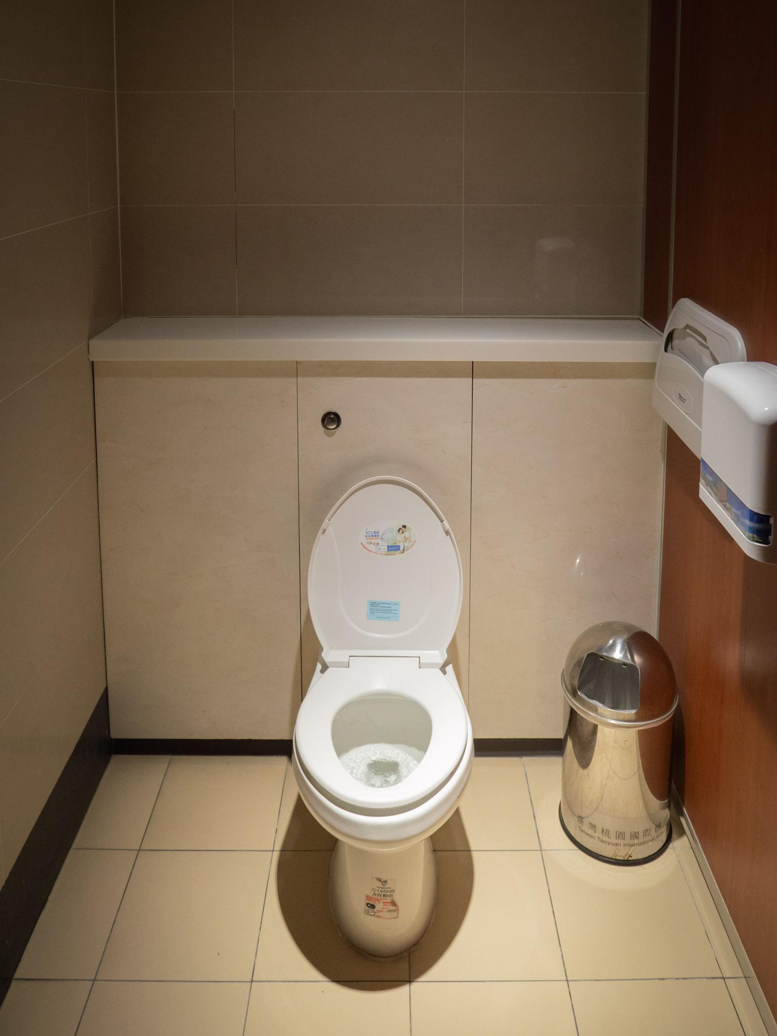 台北空港の清潔なトイレ 明け放れた便座の蓋 脇に置かれたゴミ箱の存在感