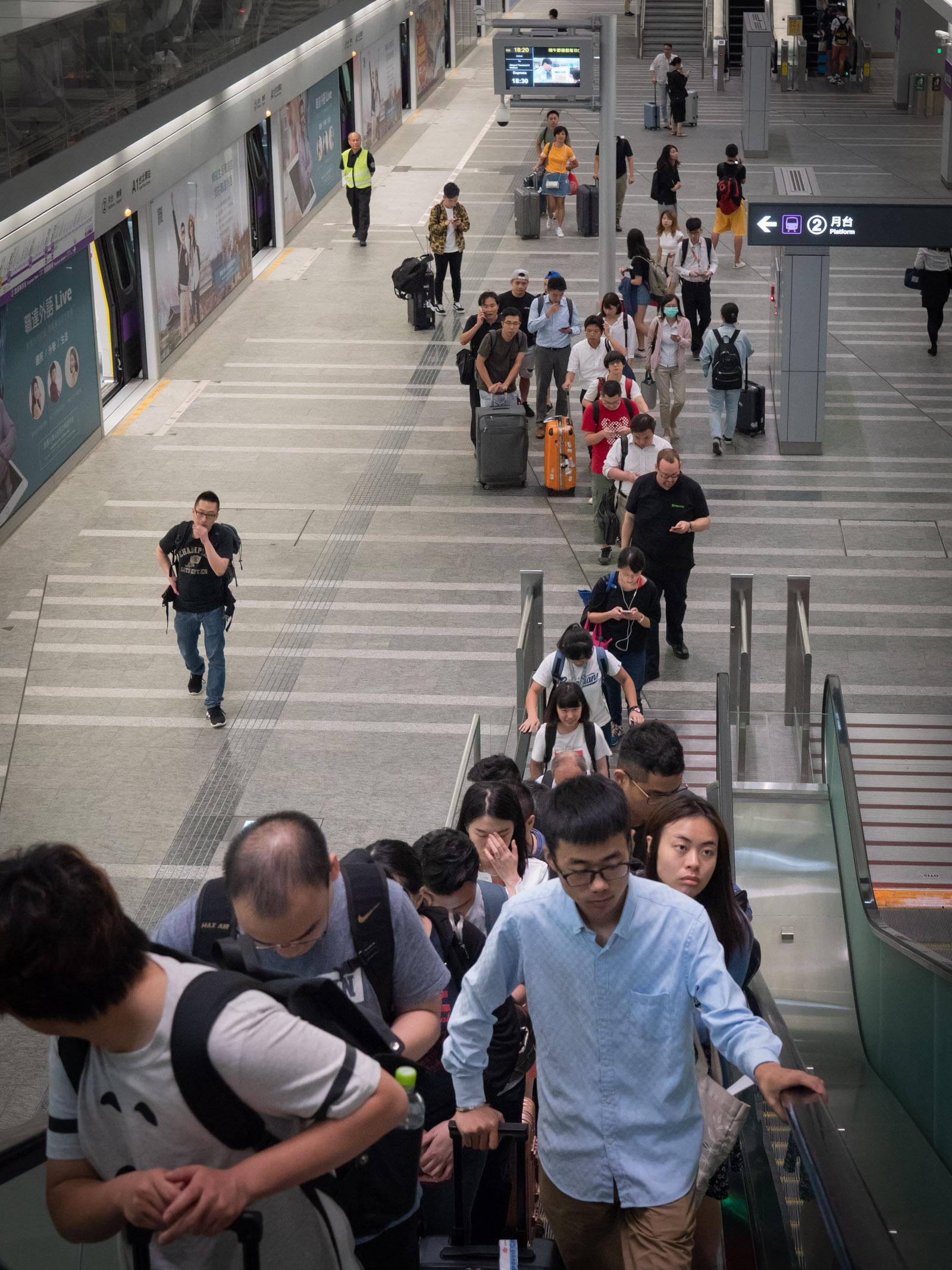 空港MRTの台北駅ホーム エスカレーターで昇る降車客
