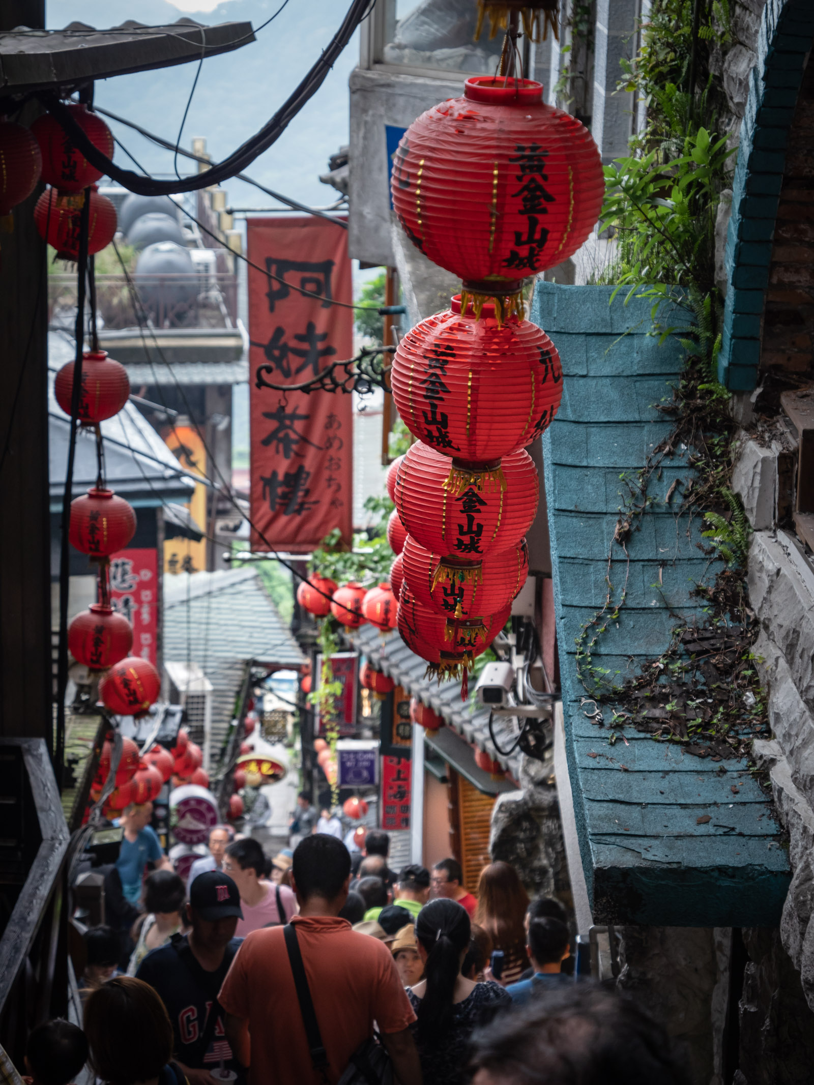 提灯が並ぶ「 阿妹茶樓」へ続く急な下り坂と行き交う大勢の人々