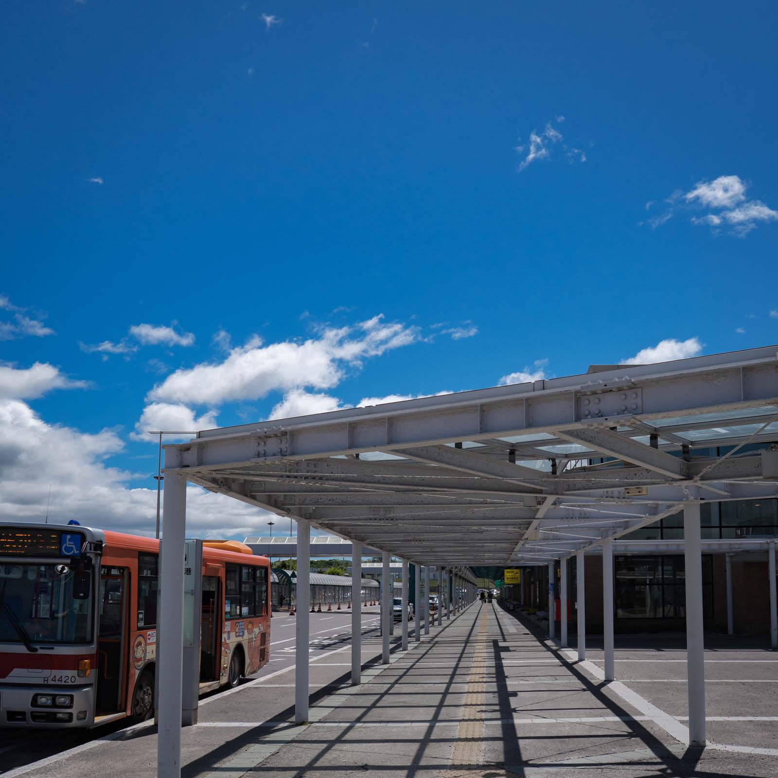 晴れ渡った空と函館空港到着ゲート前のバス亭