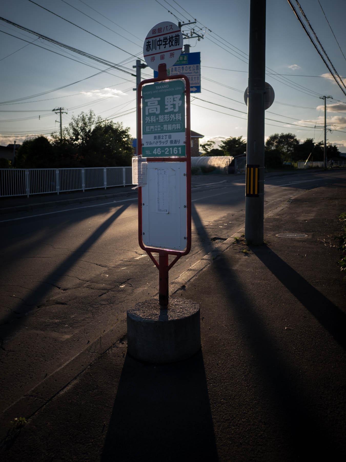 逆光のバス亭(赤川中学校前)と夕陽が作る長い影