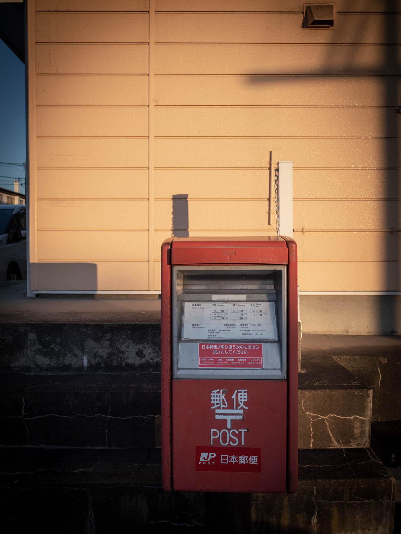 夕陽に染まりゆく壁と郵便ポスト