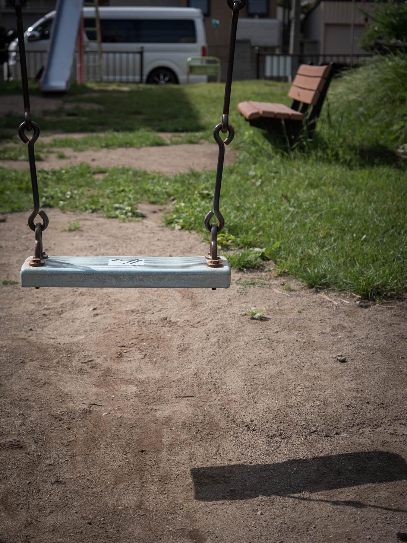 誰もいない公園 自らが落とした影に浮かぶブランコ