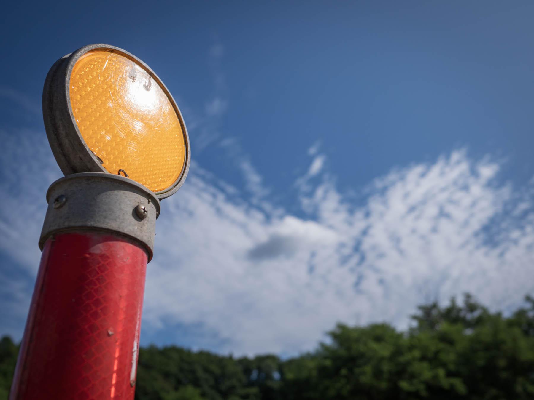 赤いポールと黄色い反射灯と青い空