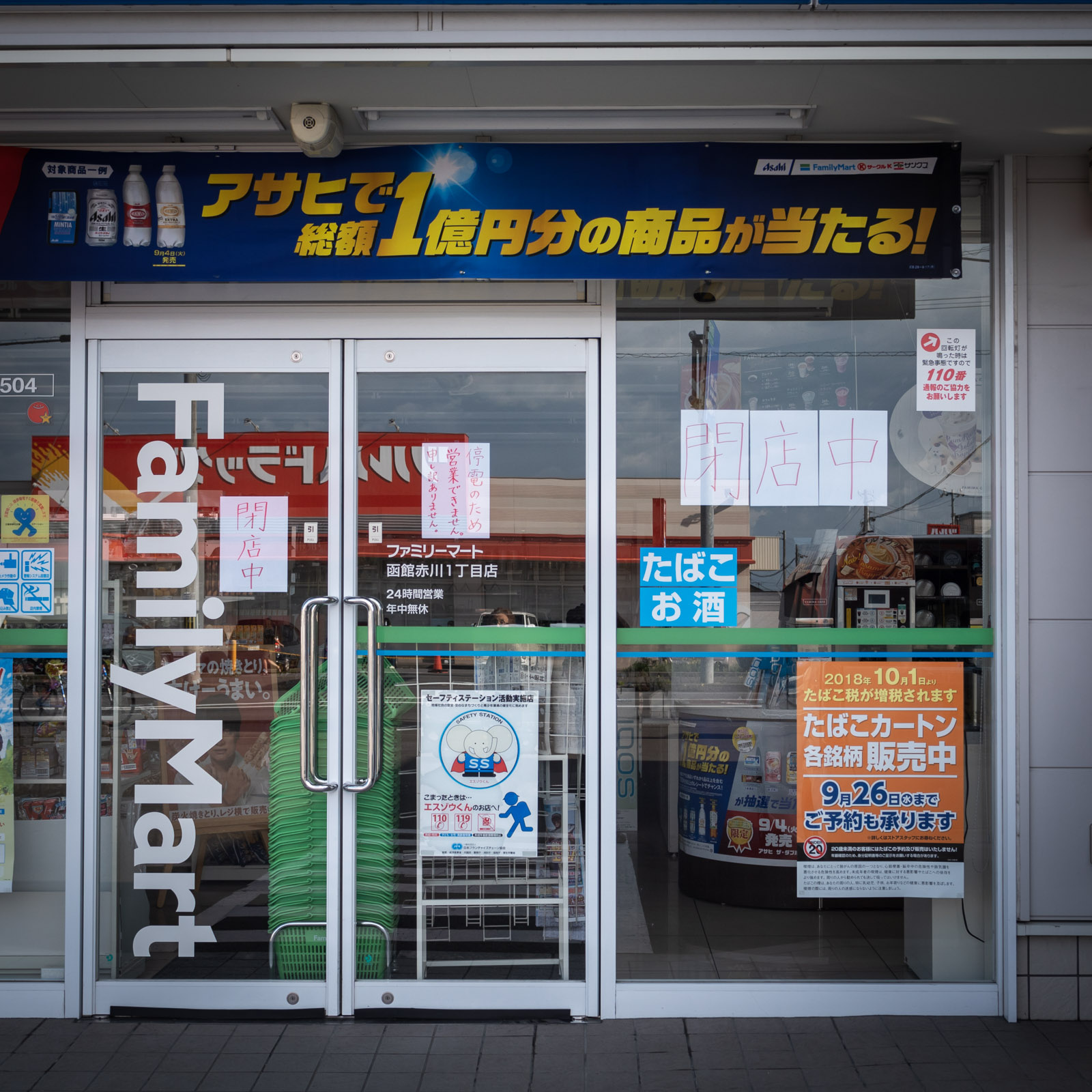 停電の朝、閉店を知らせる紙が貼られたファミリーマートの入口