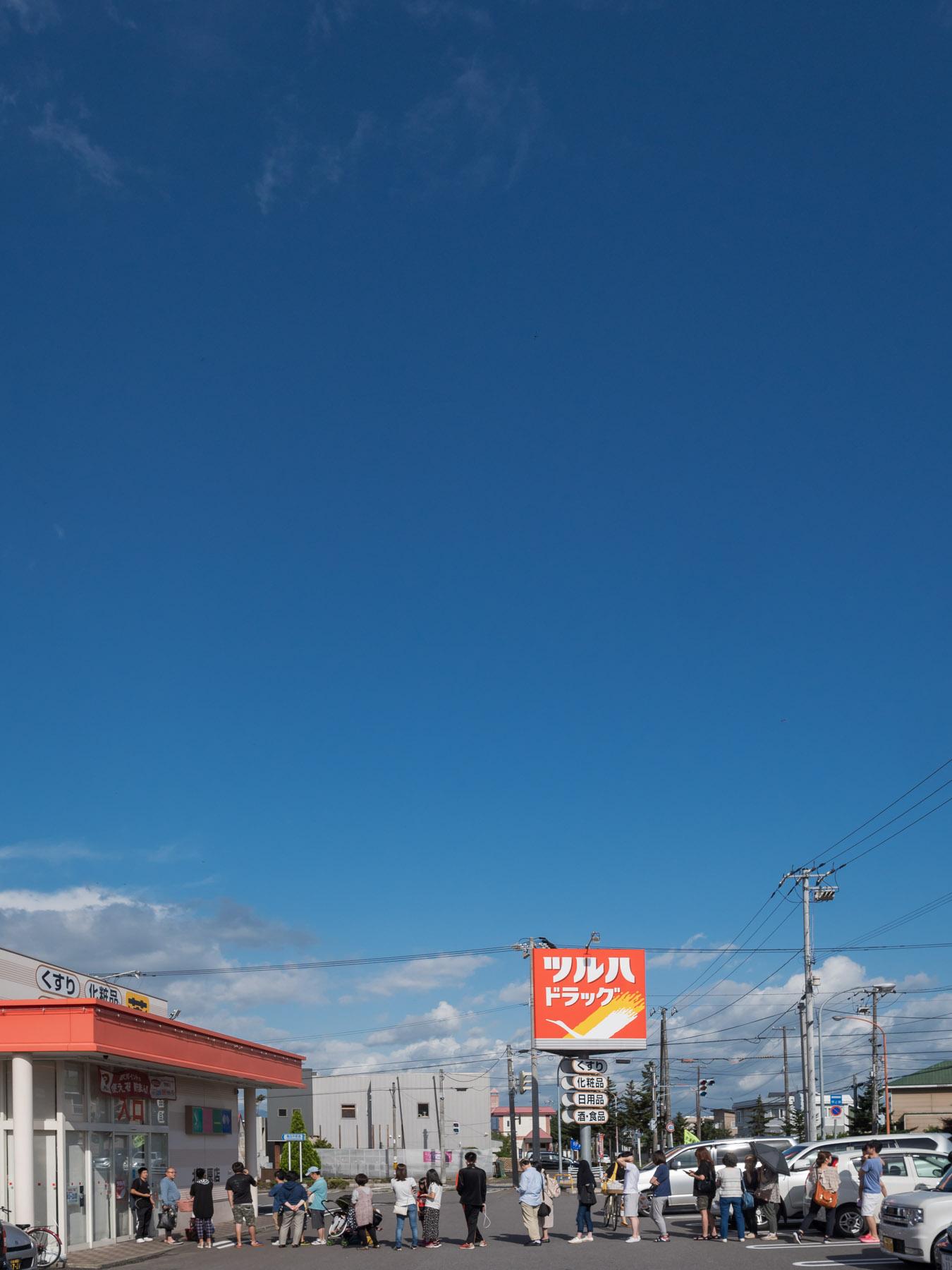 ツルハ開店を待つ行列と晴れ渡る空