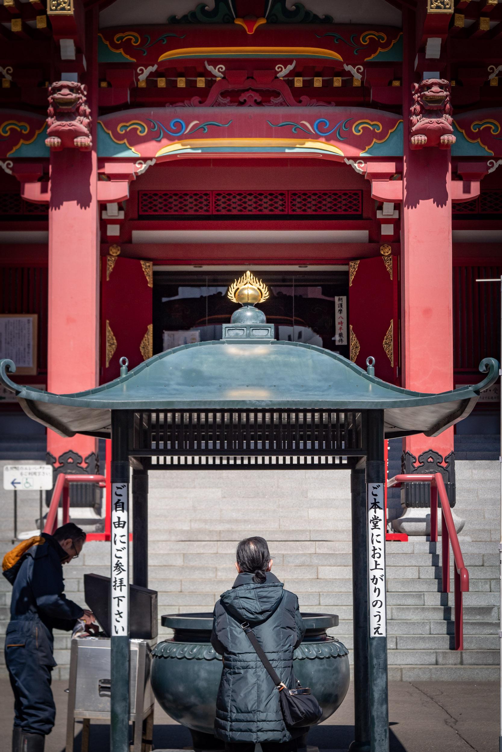 青空の下、ビルの谷間の成田山札幌別院新栄寺で祈祷する参拝客 DMC-GX8 + LEICA DG 12-60mm
