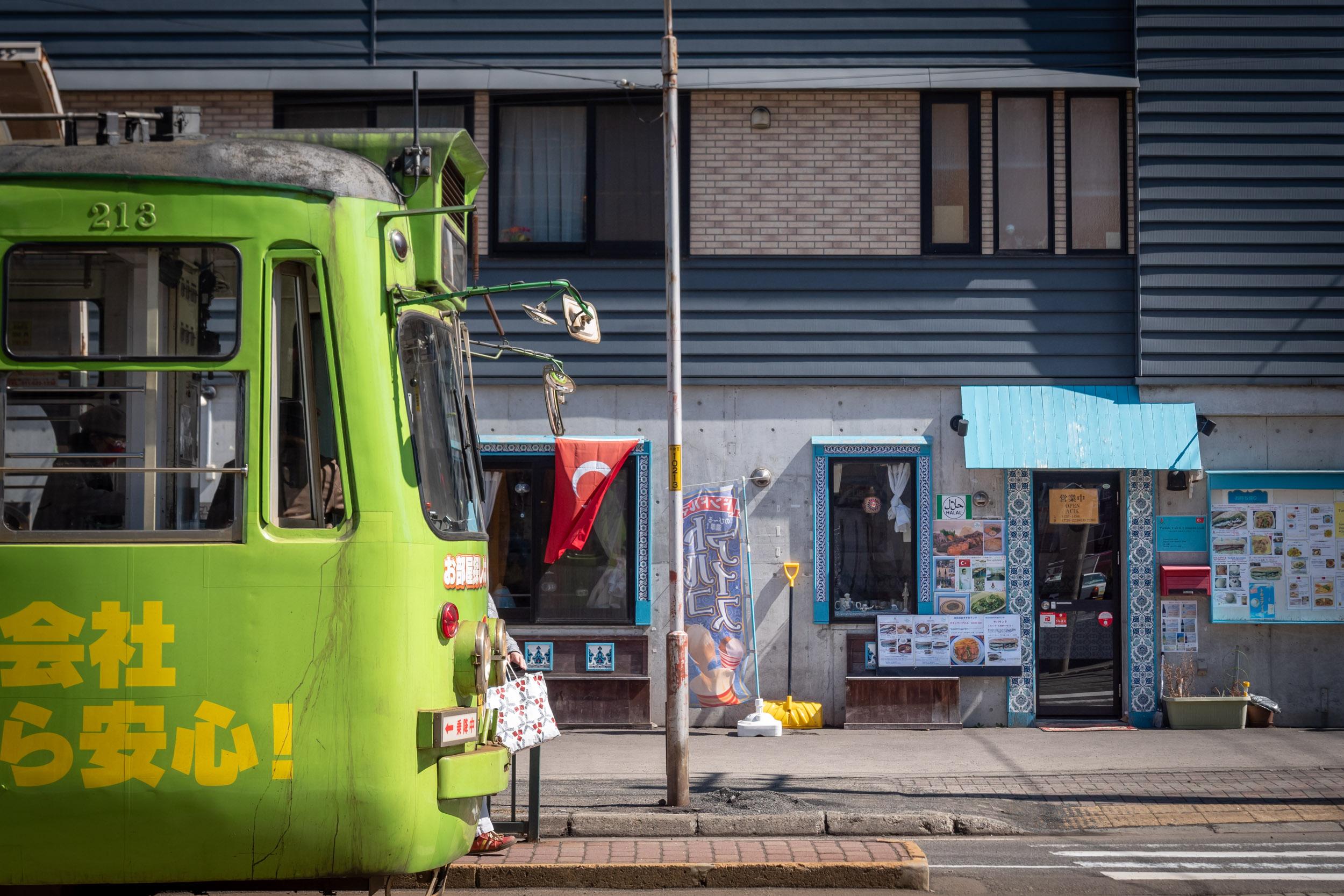 札幌市電西線6条駅でラーレをバックに停車中の路面電車 DMC-GX8 + LEICA DG 12-60mm