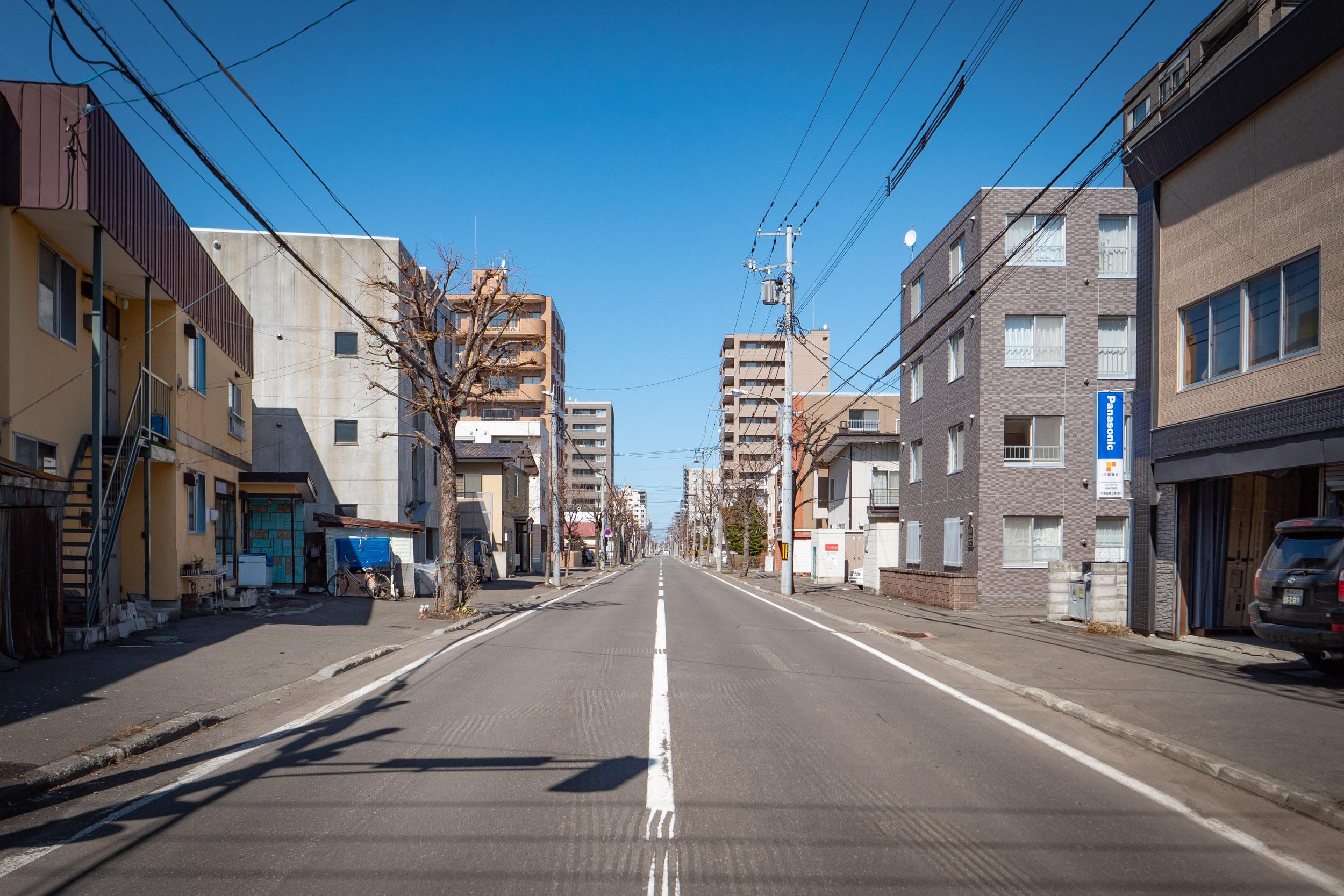 札幌市中央区南6条西23丁目あたりの街並み 青空の下どこまでも真っ直ぐに続く道通り DMC-GX8 + LEICA DG 12-60mm