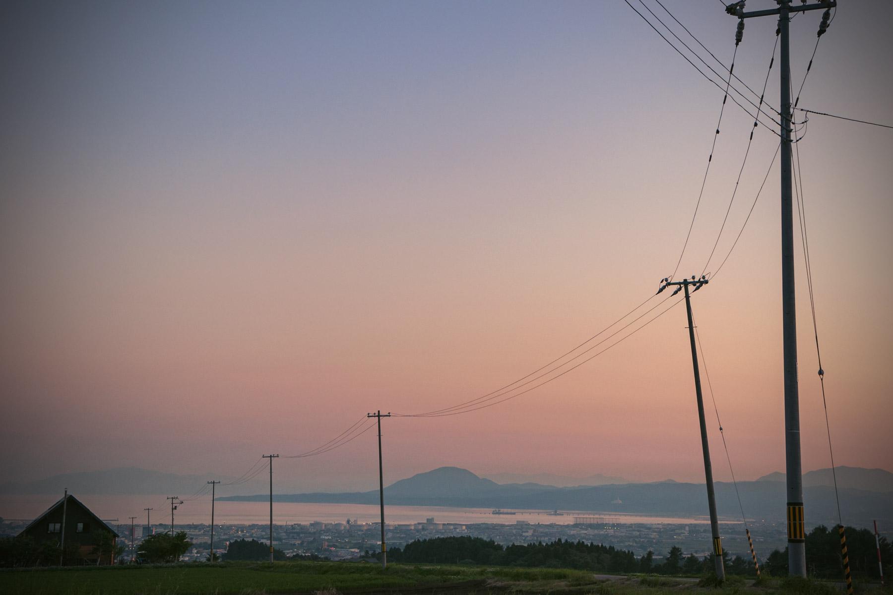 函館市亀田中野町「石川の丘」から眺める宵闇迫る函館湾 茜色の空に連なる電信柱のシルエットと海へ連なる一本の道