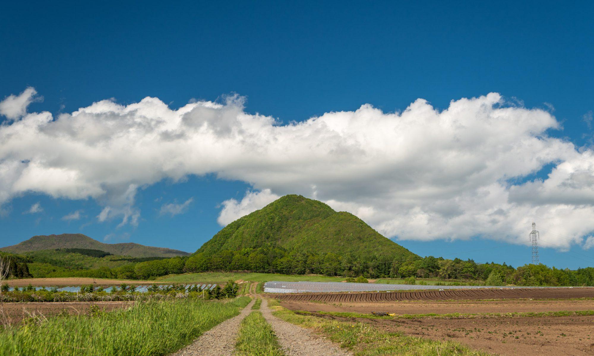 紺色の空と白い雲を冠する深緑の庄司山に伸びる道